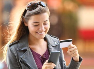 Teenage girl shopping on smartphone with credit card